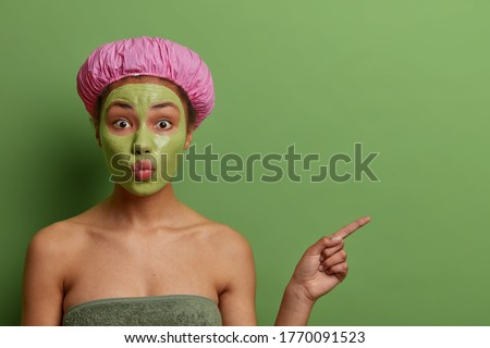 Lovely ethnic woman with folded lips, applies cosmetic mask on face, removes bleakheads, wears bath hat and wrapped in towel, shows blank space on green background, advertizes beauty product #1770091523