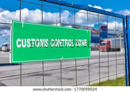 Customs clearance sign on the territory of the logistics customs terminal, with temporary storage of goods at the bonded warehouse. Trucks stand near the unloading and loading area.