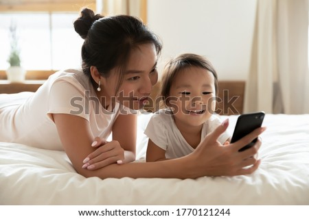 Smiling young asian ethnic woman lying on cozy bed, showing mobile application, video game or online cartoons to funny cute little biracial adopted baby daughter, posing for family selfie in bedroom.