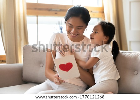 Grateful smiling young asian ethnic mother looking in handmade paper card, watching funny picture from preschool cute kid daughter, enjoying special occasion birthday wishes, feeling happiness.