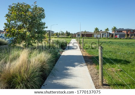 A pedestrian walkway/footpath leads to a residential neighbourhood with some modern Australian homes. Suburban view over a park with houses in the distance. Melbourne VIC Australia. Royalty-Free Stock Photo #1770137075
