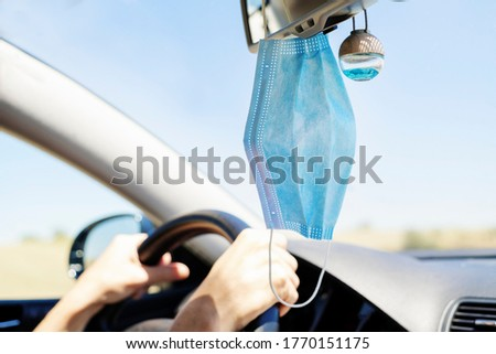 surgical mask hanging from the rear view mirror of a car selective focus Royalty-Free Stock Photo #1770151175