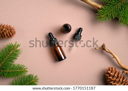 Flat lay composition with bottles of conifer essential oil on beige background. Natural organic cosmetics with pine tree branches and cones Royalty-Free Stock Photo #1770151187