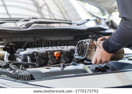 Mechanic man holding starter motor of the car on working table in repair and maintenance garage  Royalty-Free Stock Photo #1770173792