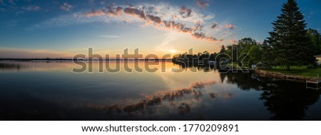 Cottage lake in Canada - Beautiful sunrise/sunset clouds reflecting in a lake at a cottage. Quiet, peaceful, serene. Gorgeous clouds in sky. Balsam Lake Kawartha Lakes, Canada Royalty-Free Stock Photo #1770209891