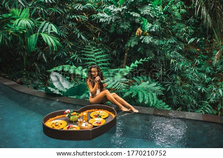 Girl relaxing and eating floating breakfast in jungle pool on luxury villa in Bali. Valentines day or honeymoon surprise. Tropical travel lifestyle. Black rattan tray in heart shape. #1770210752