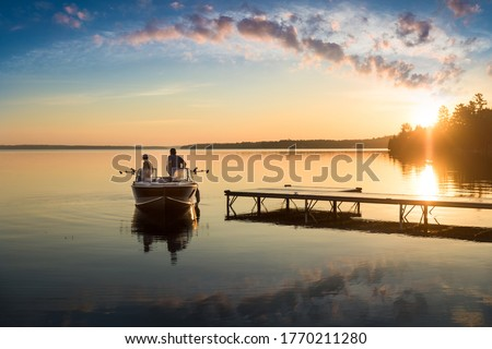 Cottage Life - Father and son fishing on a boat at sunrise/sunset at the peaceful cottage in Kawartha Lakes Ontario Canada on Balsam Lake Royalty-Free Stock Photo #1770211280