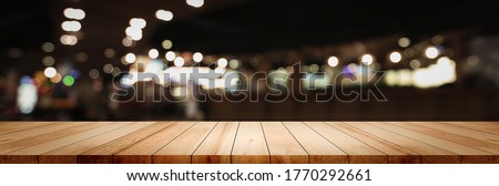 Panoramic empty clean wood counter table top on blur street night cafe background use for pub coffee shop montage dark scene, Blurry wide wooden texture shelf bar in luxury restaurant kitchen backdrop Royalty-Free Stock Photo #1770292661