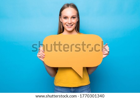 Young woman holding a speech bubble on blue background