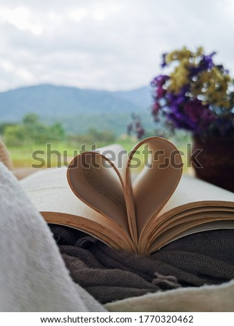 open book with a pages curled into heart shape with an amazing view of a lake and mountain.