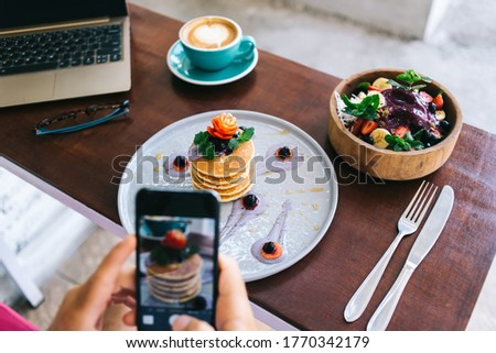 Cropped image of male blogger making photo of delicious food for lunch break sitting in cafe, selective focus on plate with pancakes stack decorated with fruits and berries for healthy brunch