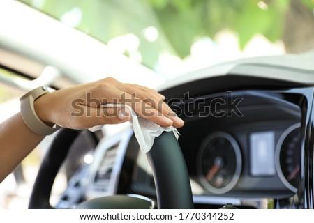 Woman cleaning steering wheel with wet wipe in car, closeup. Coronavirus pandemic Royalty-Free Stock Photo #1770344252