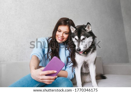 Happy young woman taking a selfie with her husky dog at home