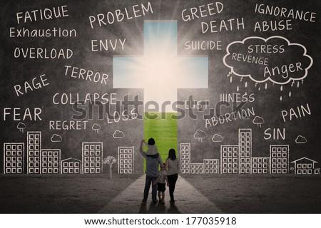 Christian family walking towards Cross of Jesus outdoor
