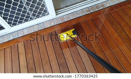 Australian spotted gum deck being stained for the first time Royalty-Free Stock Photo #1770363425