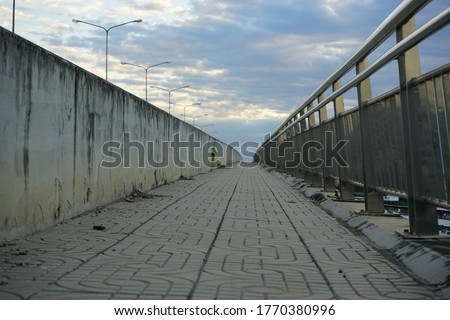 Sidewalk on the bridge with cloudy background #1770380996