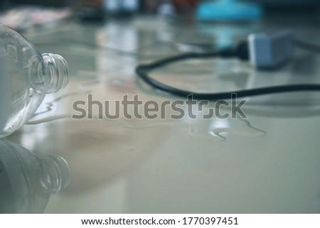 the water overturn from plastic bottle with  plug power cord plugged in In the area there is water in the house, a sign of danger to life on blurry  Electrical appliances on room background