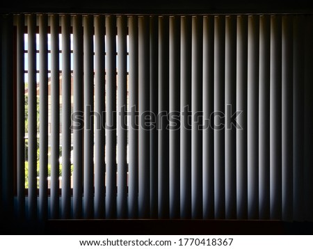 Vertical blind curtain. Behind the dark vertical blinds curtain. Inside the dark room behind the vertical white blinds. #1770418367