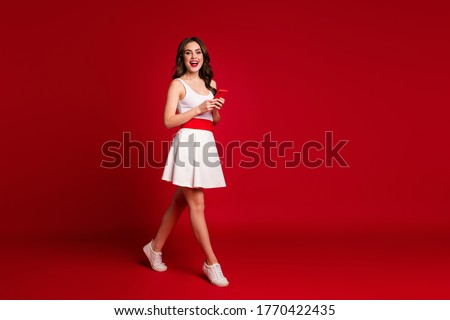 Full size profile photo of pretty cheerful lady good mood hold telephone walking street friends meeting writing sms wear white short dress shoes isolated red color background