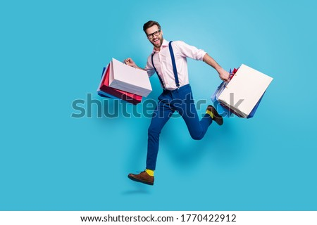 Full length profile photo of handsome business man carry bags jump high buy vacation stuff shopping center store mall wear specs shirt suspenders pants boots isolated blue color background #1770422912