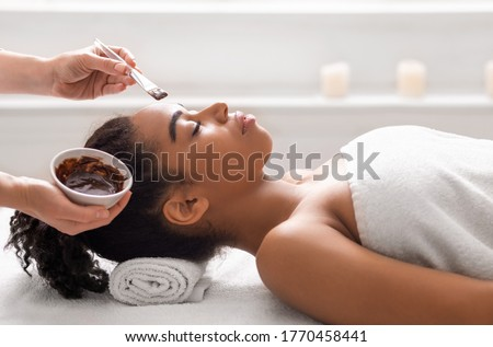 Facial treatment concept. Side view of african woman getting facial mask at spa Royalty-Free Stock Photo #1770458441
