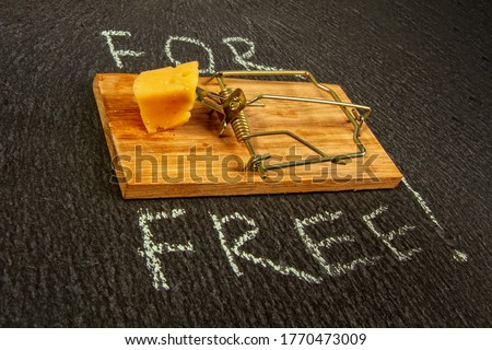 conceptual picture of a mousetrap with a piece of cheese and the inscription FOR FREE on a dark background