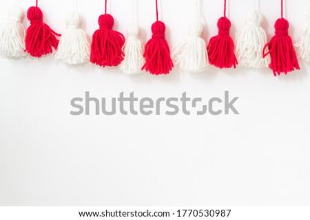 brushes from yarn of red and white color on a white background. Space for copy space. DIY yarn brushes. Garland. Garland of yarn. Pampushki from yarn. Children's creativity #1770530987