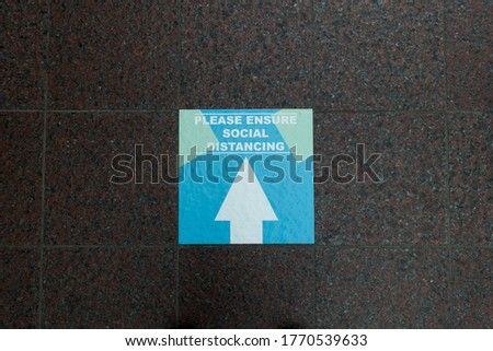 A square floor sign with white arrow on blue says 'please ensure social distancing' on a tiled floor.Image