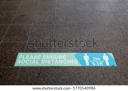 A rectangular floor sign with symbols of two people and lettering saying 2m and 6.5 feet says 'please ensure social distancing' on a tiled floor.Image