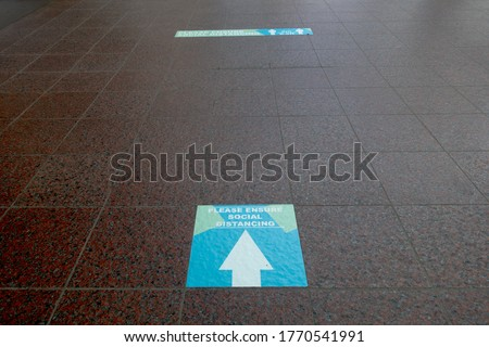 A floor sign with arrow says 'please ensure social distancing' on a tiled floor with further sign in distance.Image