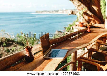 Open laptop with black screen  on wooden table work space outdoors with amazing view on the ocean. Laptop on sea view backdrop #1770576503