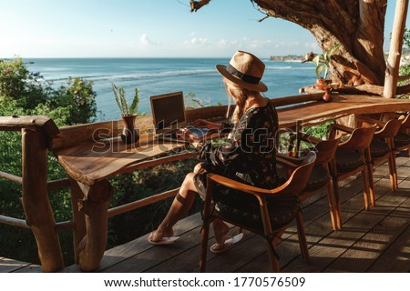 Freelance concept. Pretty young woman using laptop in cafe on tropical beach in outdoor cafe terrace with sea view. Work and travel Royalty-Free Stock Photo #1770576509