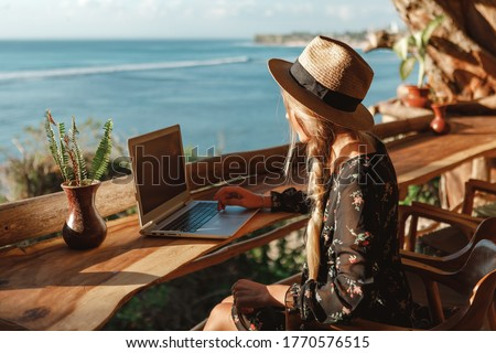 Business woman working with computer on the beach.  Freelance concept. Pretty young woman using laptop in cafe on tropical beach Royalty-Free Stock Photo #1770576515