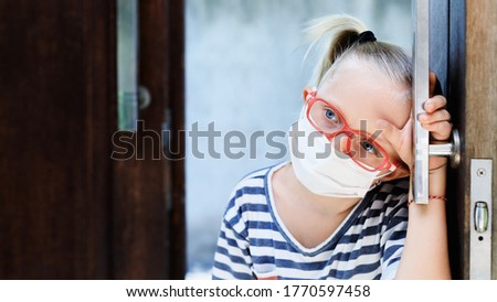 Little child looking unhappy and depressed after staying at home due banned street activity. Kid wearing medical face masks go out for outside walk, ending coronavirus Covid-19 disease quarantine.