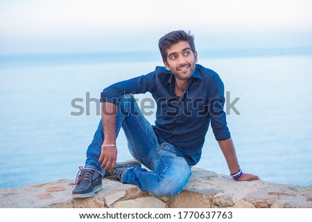 Man smiling looking to the side happy celebrating freedom while sitting on a concrete wall bridge above the sea. Positive person, peace mind concept. Free happy guy enjoying sunset #1770637763