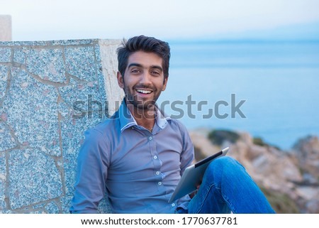 Man smiling happy while using pad looking to blue sky while sitting on a concrete bridge above the sea taking deep breath enjoying freedom at sunset sea on background. Cheerful excited cool person #1770637781
