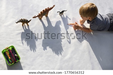 child draws with a pencil contrasting shadows from toy dinosaurs. drawing a preschooler,  ideas for children's creativity. Interesting activities for development of creative thinking