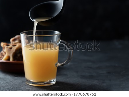 Homemade Beef Bone Broth in Glass Storage Jar on the black background. Bones contain collagen, which provides the body with amino acids, which are the building blocks of proteins Royalty-Free Stock Photo #1770678752