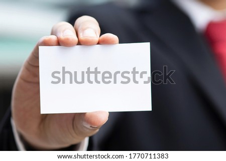 business man in hand hold show blank white credit name card display front mock up with rounded corners. Business branding concept.