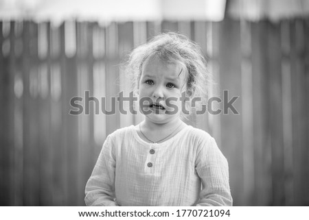 Black and white photo, a small pretty girl in a white blouse against the background of an old gray fence, the baby is upset, the emotion of sadness.  #1770721094