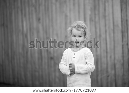 Black and white photo, a small pretty girl in a white blouse against the background of an old gray fence, the baby is upset, the emotion of sadness.  #1770721097