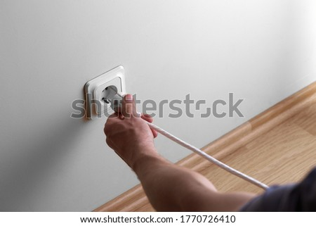 Man hand tyr to plugging electric plug a in a socket on the wall but wire is too short Royalty-Free Stock Photo #1770726410