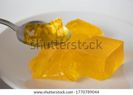 Yellow gelatine on a plate on a white background Royalty-Free Stock Photo #1770789044