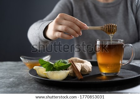 Pouring honey into the tea.Tea with honey lemon ginger mint and cinnamon stock image
