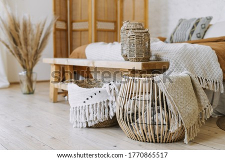 Selective focus on home decor. Comfortable bedroom in bohemian interior style with textile sheet on bed, wooden bench seat, bamboo dressing screen, dry plants in vase, wicker basket Royalty-Free Stock Photo #1770865517
