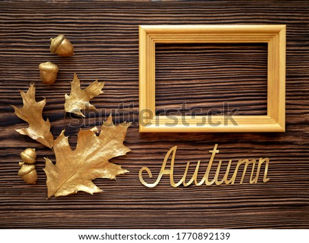 Golden autumn. Oak leaves and acorns on a wooden background. Text frame