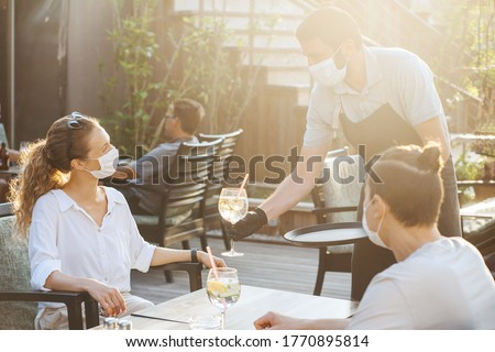 Couple with medical facemask and Waiter with gloves are keeping social distance in restaurant. Aftermath of covid-19 relief of Quarantine measures Royalty-Free Stock Photo #1770895814