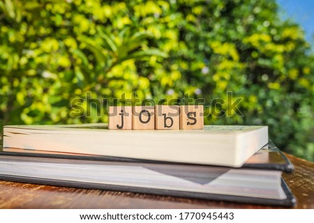 The word JOBS, letters on block cubes on top of books and wooden table with green trees, outdoor nature background. Concepts of human resources, hiring, vacancy, employment and business. Royalty-Free Stock Photo #1770945443