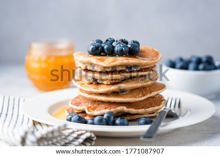 Whole wheat pancakes with blueberries and honey on a plate. Tasty breakfast food, stack of homemade pancakes Royalty-Free Stock Photo #1771087907