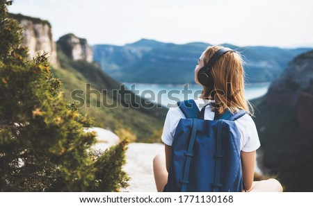 woman with backpack meditating listen to music with headphones and looking view landscape river peak mountain, female tourist with long blond hair relax after walking enjoy journey trip, copy space #1771130168